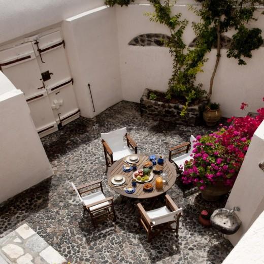 地中海風の白い漆喰で作られたギリシャ サントリーニ島のヴィラの中庭の屋外ダイニングスペースを上から