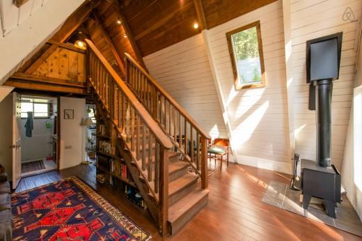森の中に建つコンパクトなAフレームの山小屋 玄関から入ったところ 中央に階段