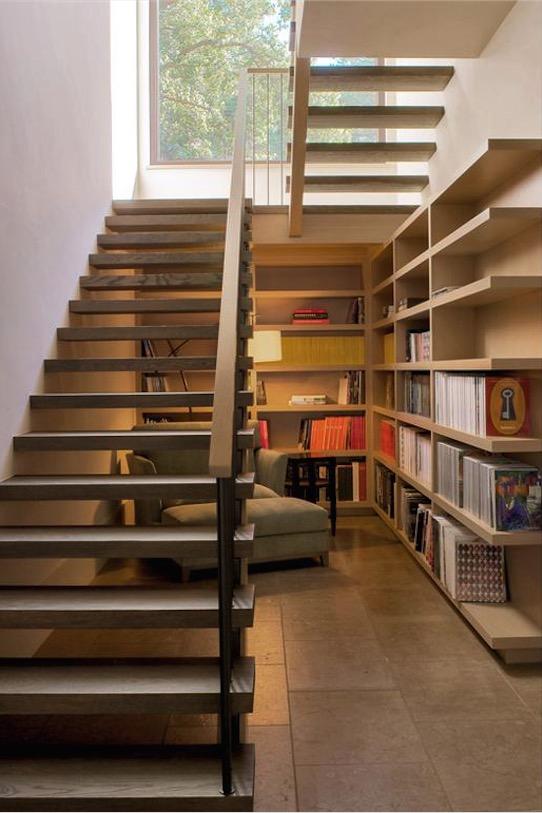 階段下に作り込まれたリーディングヌック 大きな造作本棚と座り心地の良さそうな一人掛けのソファ