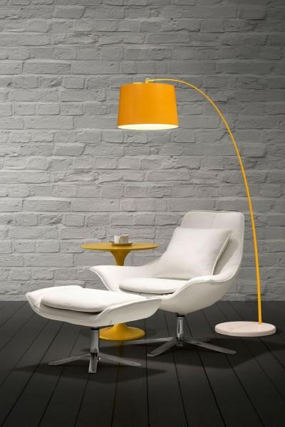 黒いフロアに一人掛けの白いソファと山吹色のデスクスタンドとテーブルの置かれた寛ぎスペース