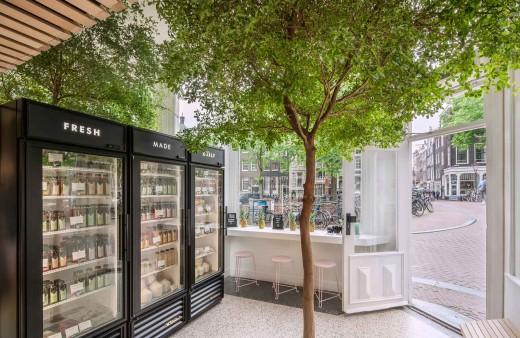 半屋外の開放的なテラス的スペースにドリンク用の冷蔵庫の置かれたフレッシュジュース・カフェテリア