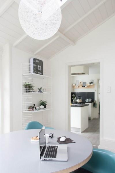 丸テーブルと天窓のある、天井の低い正方形のダイニングルームからキッチンを
