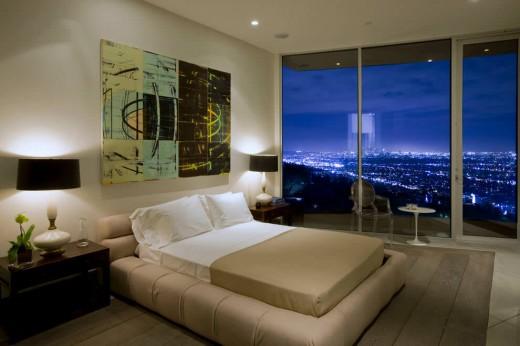 高台に建つ家の開放的な全開口スライドドアのベッドルームからの夜景