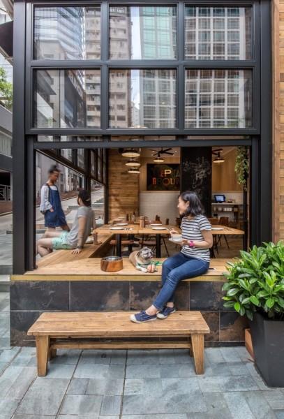 壁際に縁側的なベンチシートのある開放的なカフェのダイニング