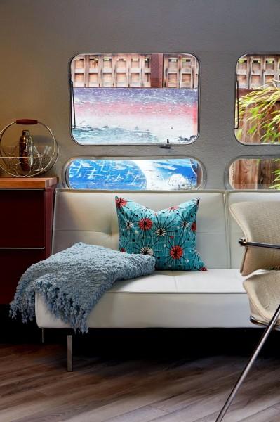 庭のウッドデッキの脇に置かれたロングボディのキャンピングトレーラーAIRSTREAMの入口正面に置かれたソファ
