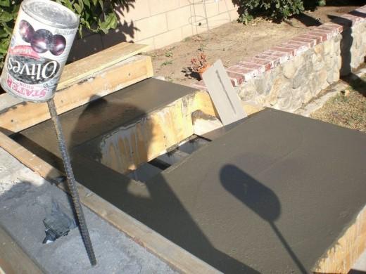 DIYで作った、レンガのカウンターやBBQグリル、シンクのある立派なアウトドアキッチン DIY18 木枠にコンクリートを流し込み、表面をフラットに整える