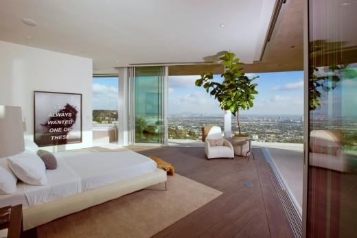 高台に建つ家の開放的な全開口スライドドアのベッドルームから街を