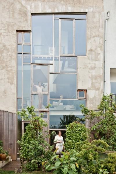 リビングの上にネットの空中リビングが作りこまれたガラス張りの家