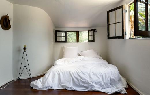 大小2つの観音開きの飾り格子窓のあるベッドルーム