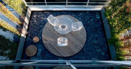 敷き詰めた石の上に円形のデッキを敷いたルーフバルコニー