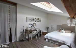 天窓のある低い天井のロフトのベッドルーム