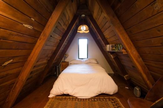 森の中に建つコンパクトなAフレームの山小屋 2階のロフトベッドルーム 勾配天井下の包まれ感