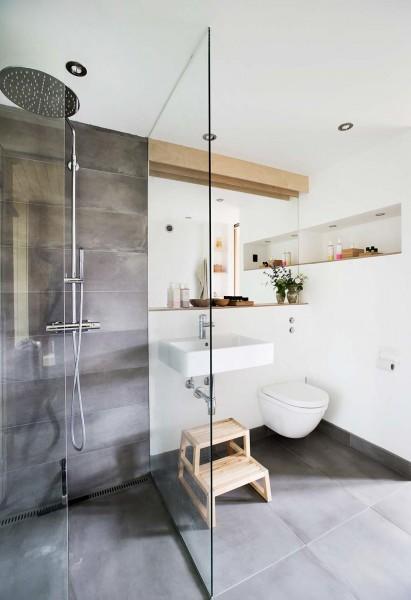 オーバーヘッドシャワーのあるガラス張りの明るいバスルーム