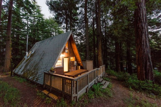 森の中に建つコンパクトなAフレームの山小屋の外観 奥のテラス側からjpg