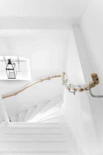 枝で作った手すりとニッチ状の出窓のある白いペンキ塗りの可愛らしい階段を上から見下ろす