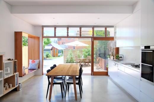 ダイニング・キッチンと庭の脇のウッドデッキのテラスが、ベンチ付きの大きな開口窓でつながる家