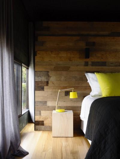 レモンイエローの枕とテーブルランプのあるベッドルーム